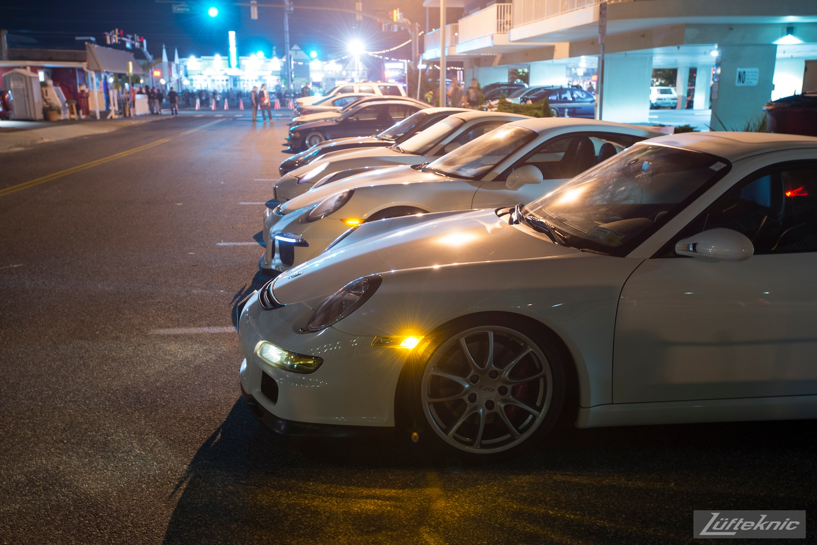 A misty nighttime picture showing a 997 GT3 with 991 and 996 type gt3 cars with their lights on