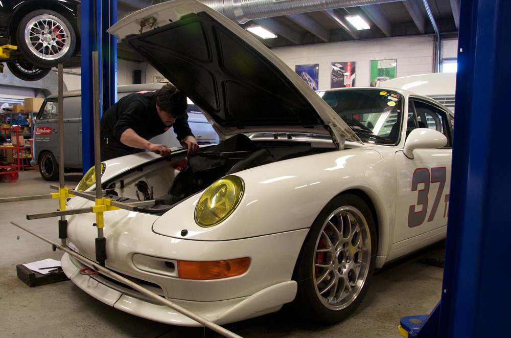 A Lüfteknic technician working on a white 993 911 race car.