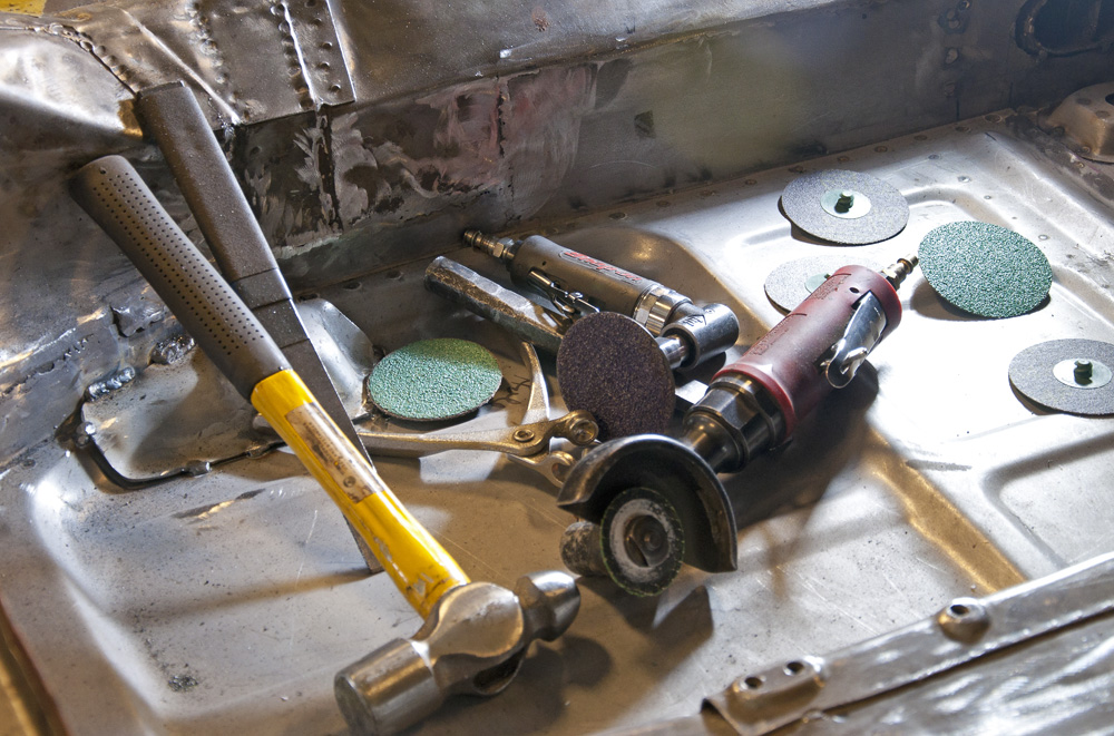 A close up picture of body and metal working tools on the floor pan of an old Porsche
