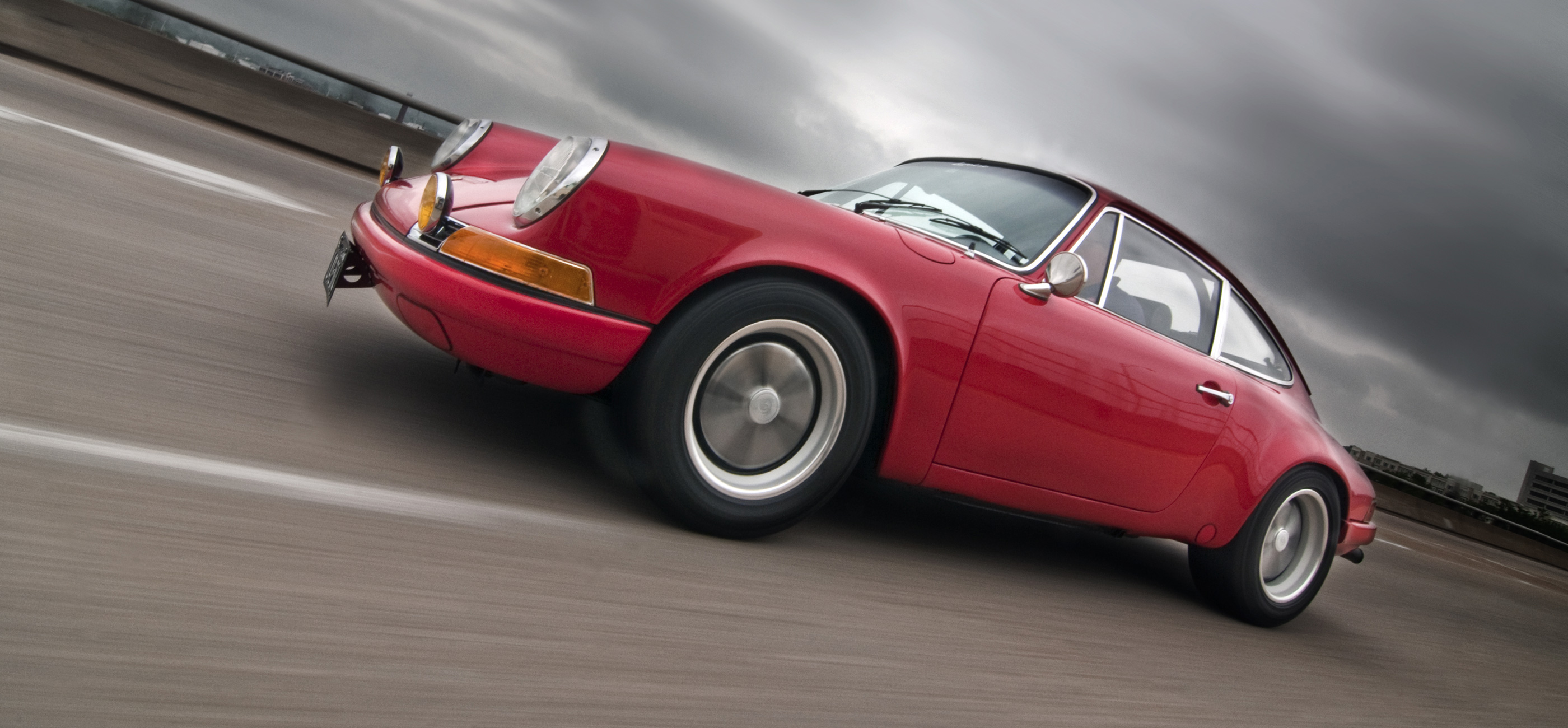 A pacing shot of a red 1970 911E with dark clouds.