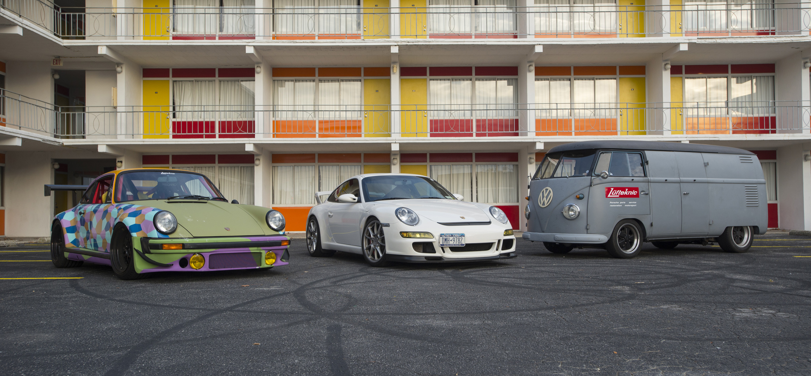 Projectstuka, a 997 GT3 and the Porschebus in front of a colorful hotel.