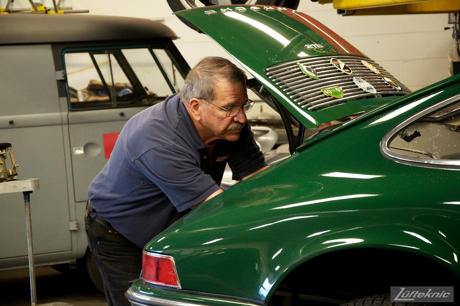 A Lufteknic employee working on the engine in a green Porsche 912.