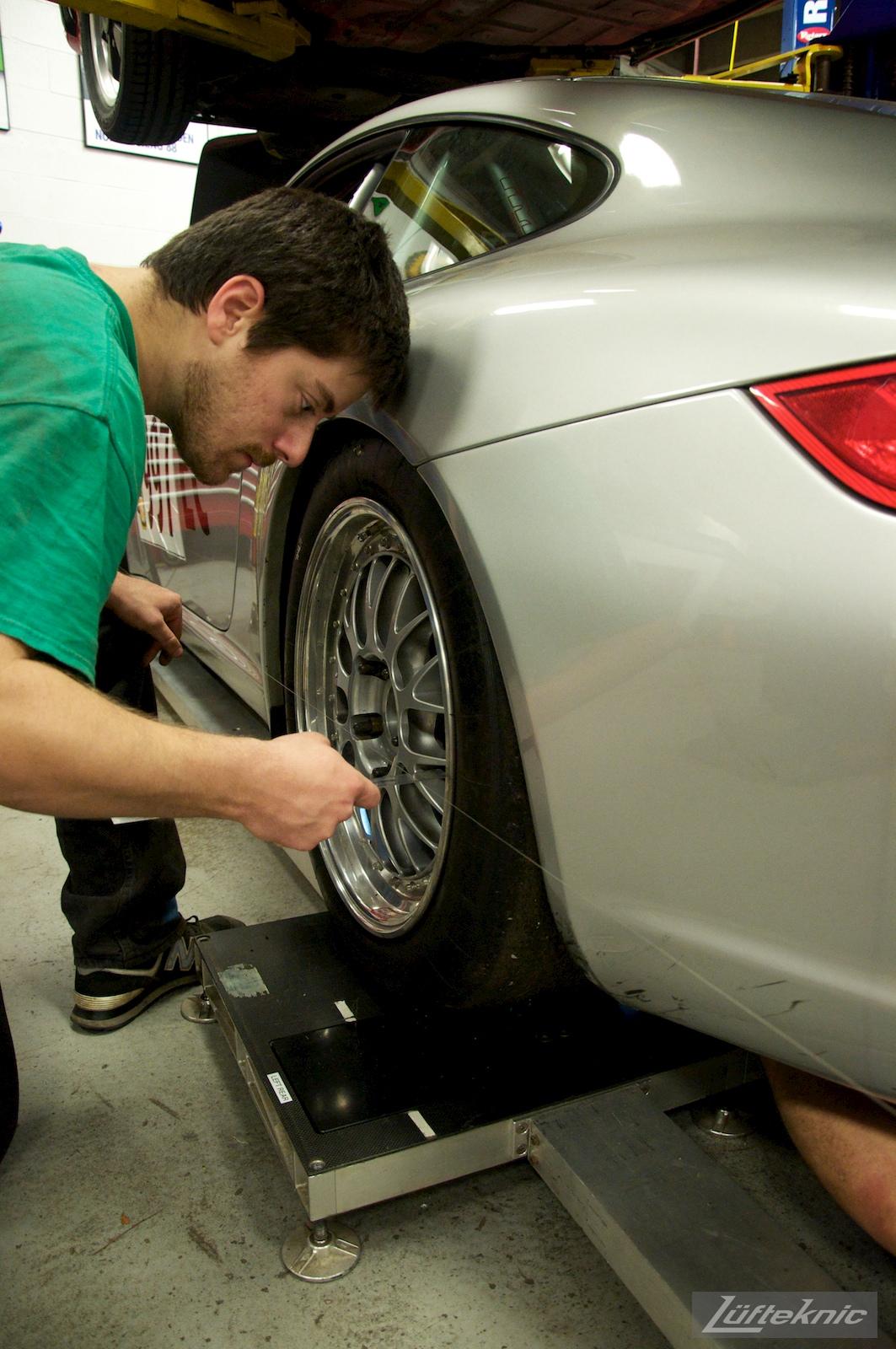 A Lufteknic employee measuring toe alignment settings on a silver Porsche 997 911 race car.