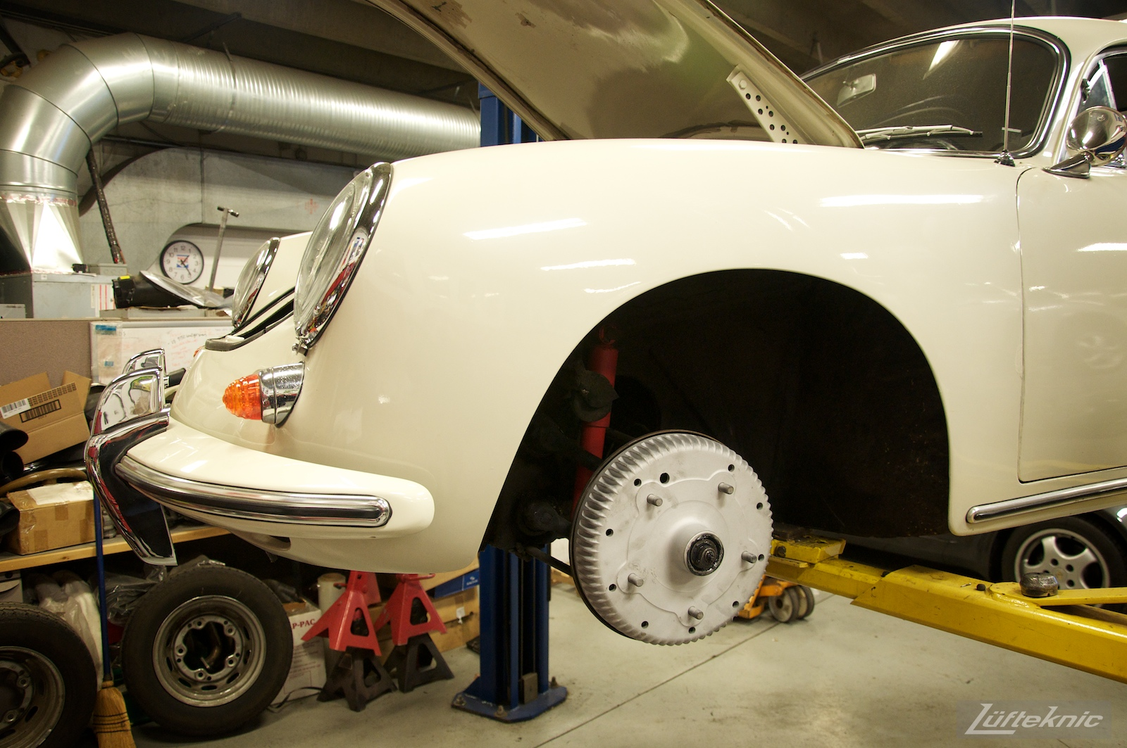 A white Porsche 356 on a lift at Lufteknic with the wheel removed showing a fresh brake drum