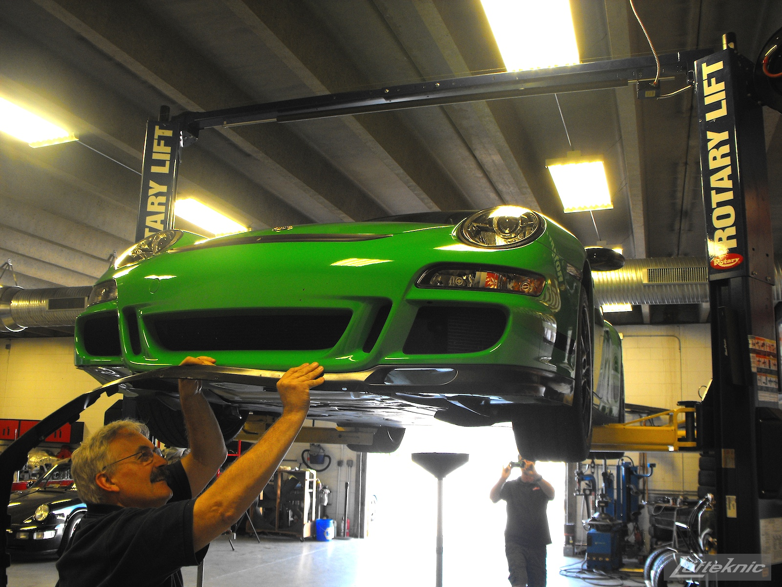 A Lufteknic employee removes the lower chin spoiler from a green Porsche 997.1 GT3 RS.