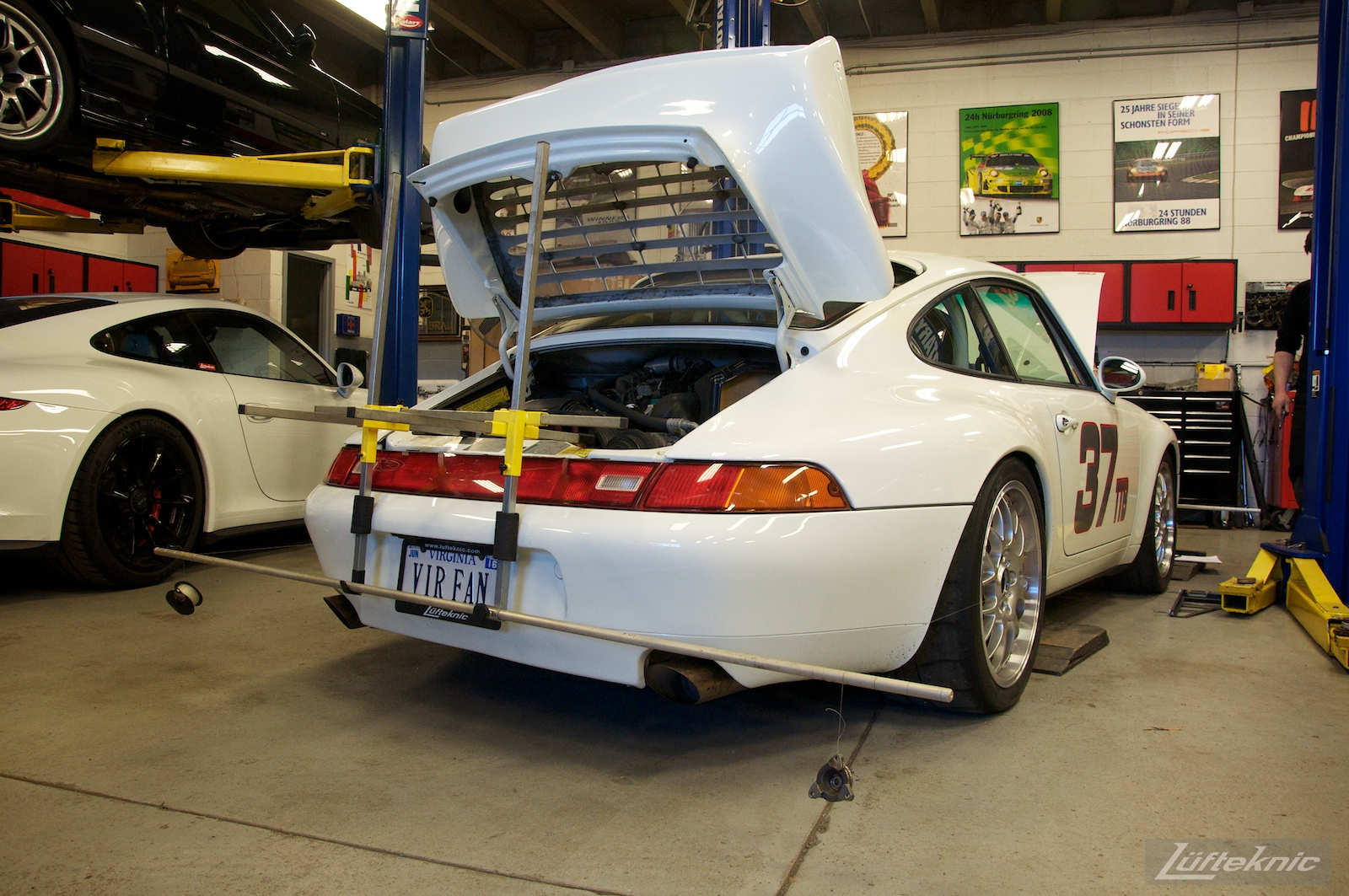 A white Porsche 993 race car inside the Lufteknic shop with alignment strings attached.