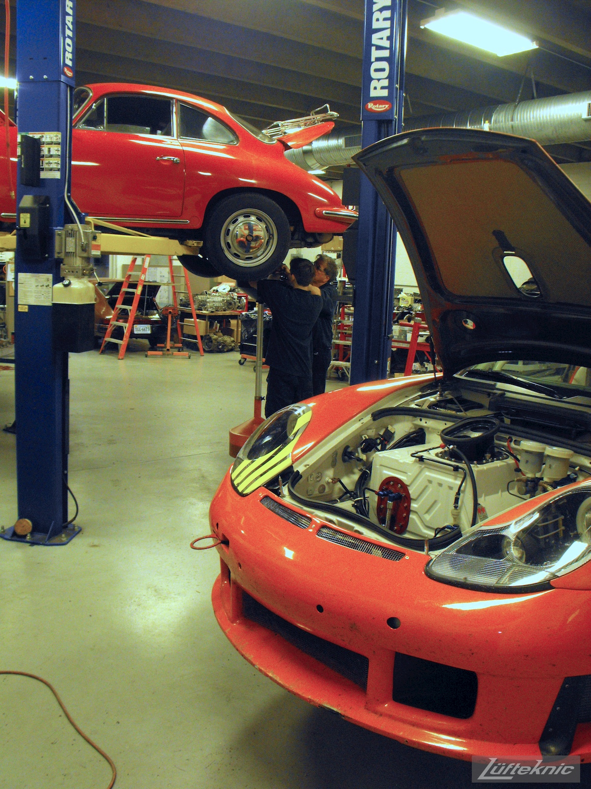 An orange Porsche RSR race car on the lift with a red 356 being worked on in the background.
