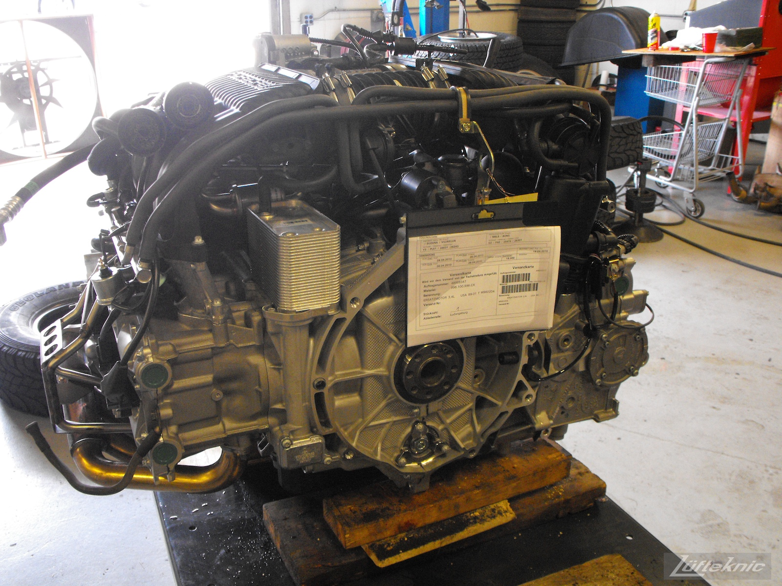 A brand new M96 Porsche motor sits on an engine table with technical sheet attached.