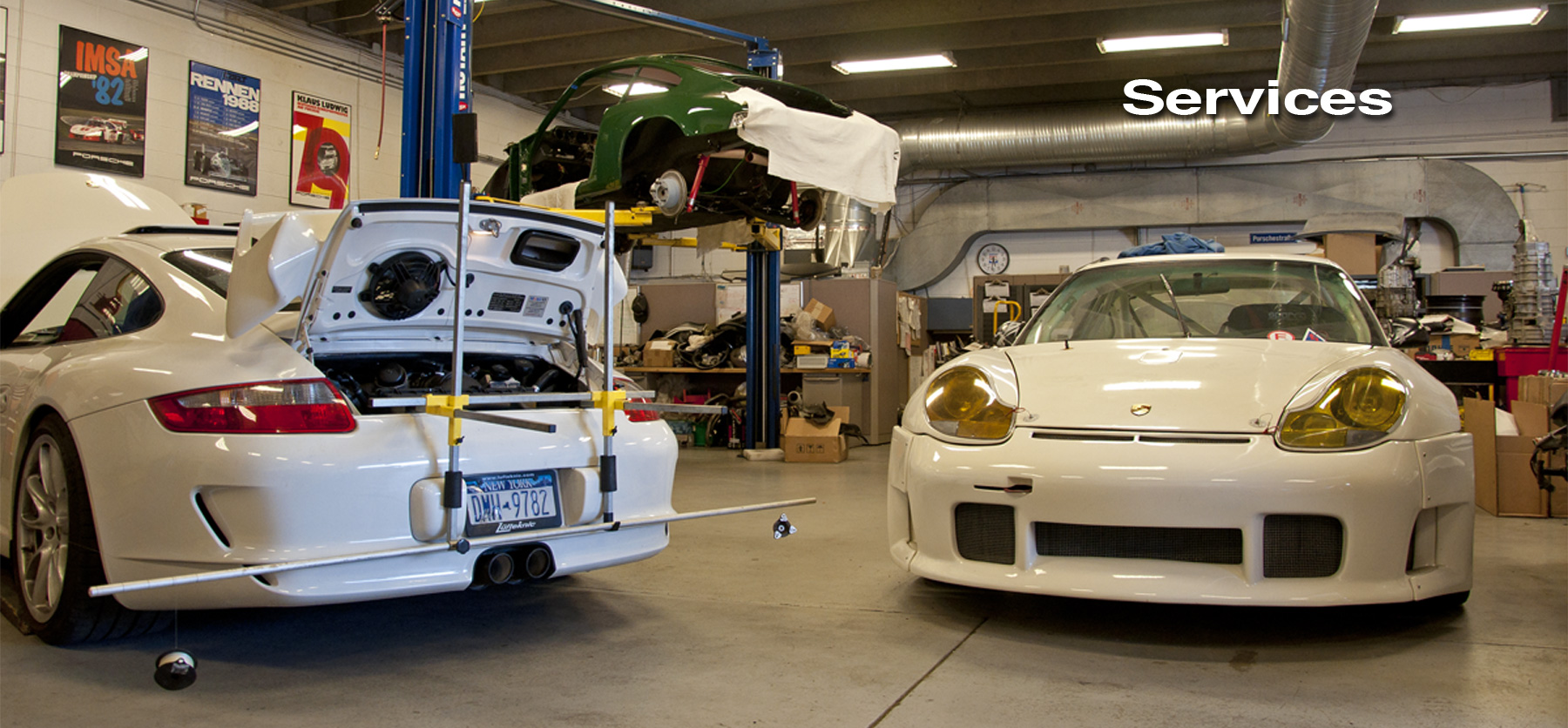 Lüfteknic services header image showing a 997 GT3, 912 and 996 GT3 RSR being worked on inside the shop.