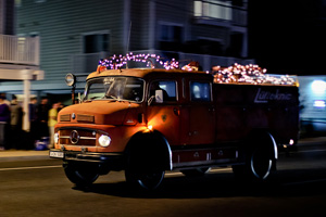 A 1964 Mercedes fire truck with christmas lights driving down coastal highway at h2oi.
