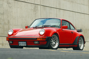 A red 930 turbo sits in a parking lot