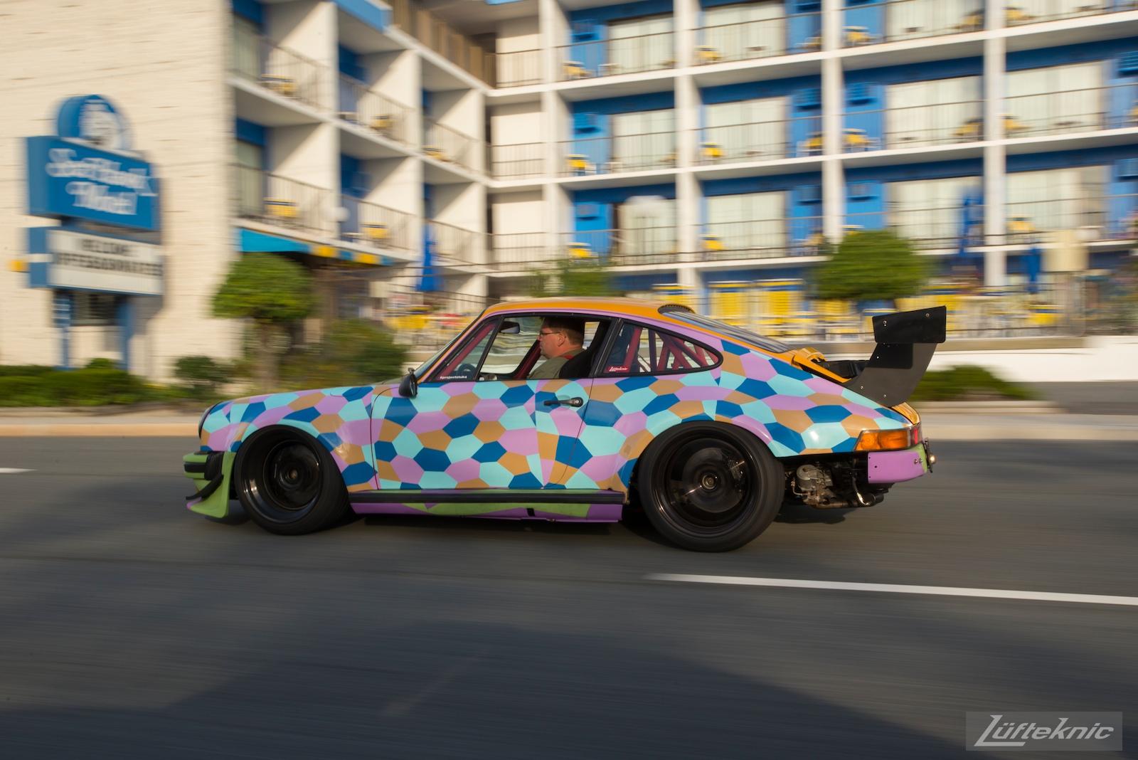 A panning shot of the Lüfteknic #projectstuka Porsche 930 Turbo driving past a hotel