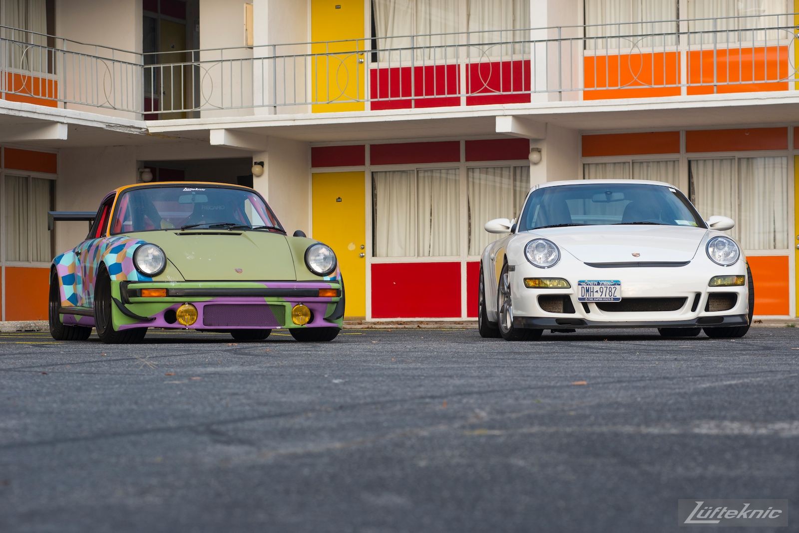 The Lüfteknic cars, including #projectstuka, porschebus and 997 GT3 pose in front of a colorful hotel.