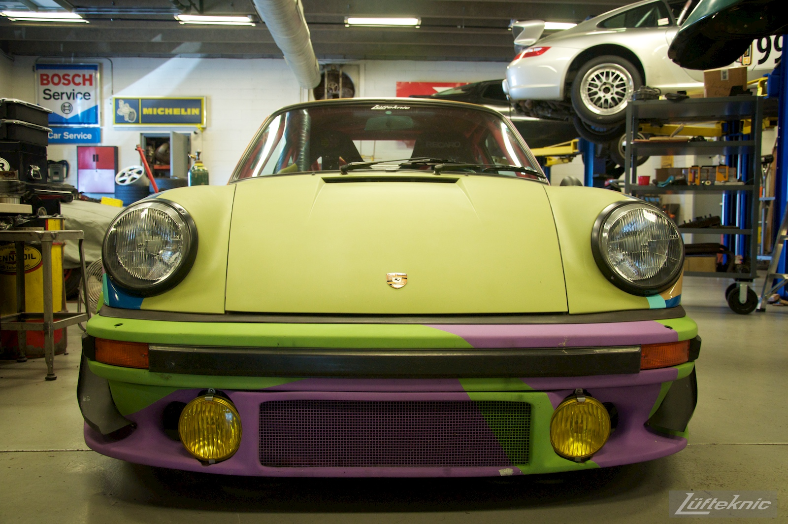 A front end picture of the Lüfteknic #projectstuka Porsche 930 Turbo with porsches being worked on in the background