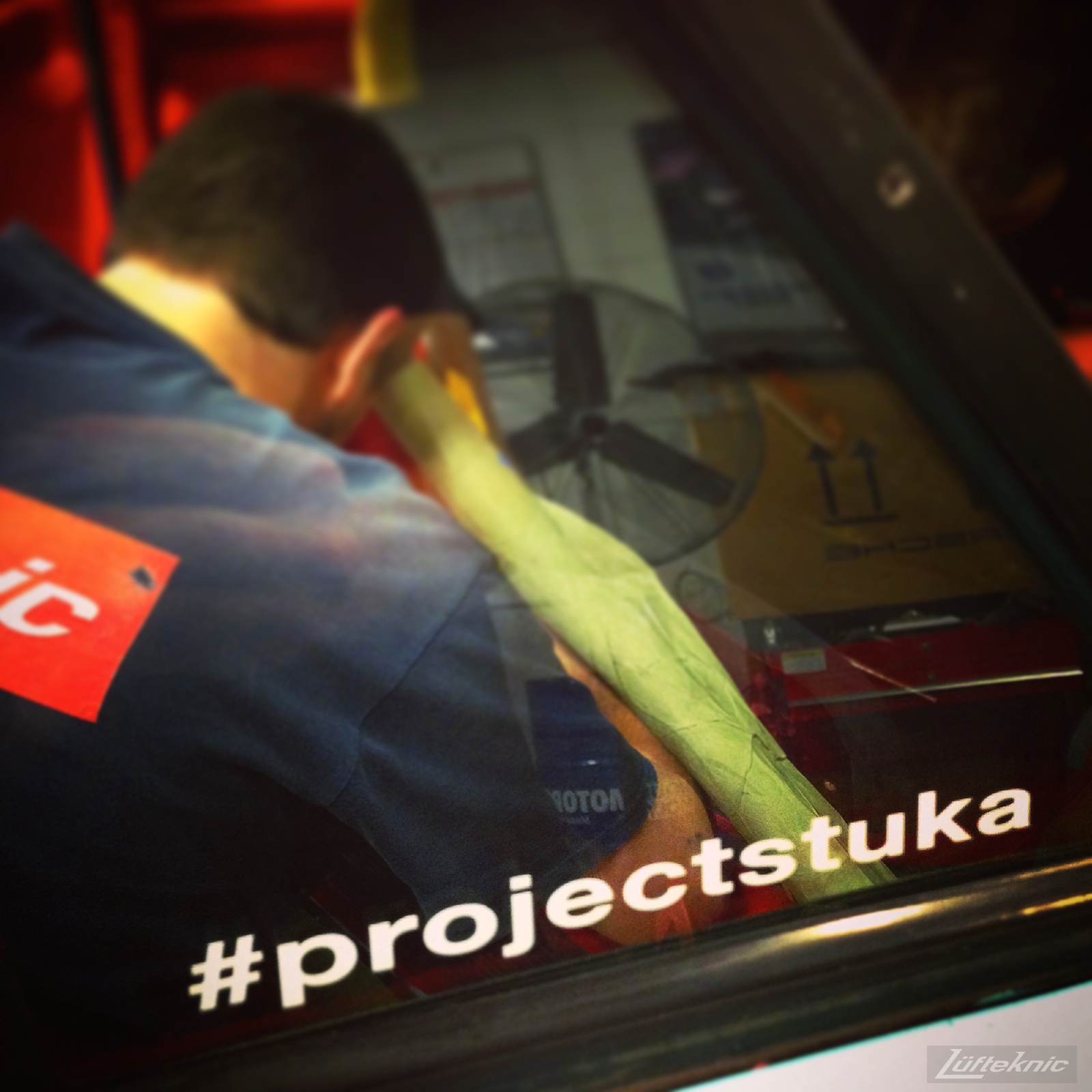 Close up picture of the #projectstuka hashtag sticker with a reflection of a lufteknic employee