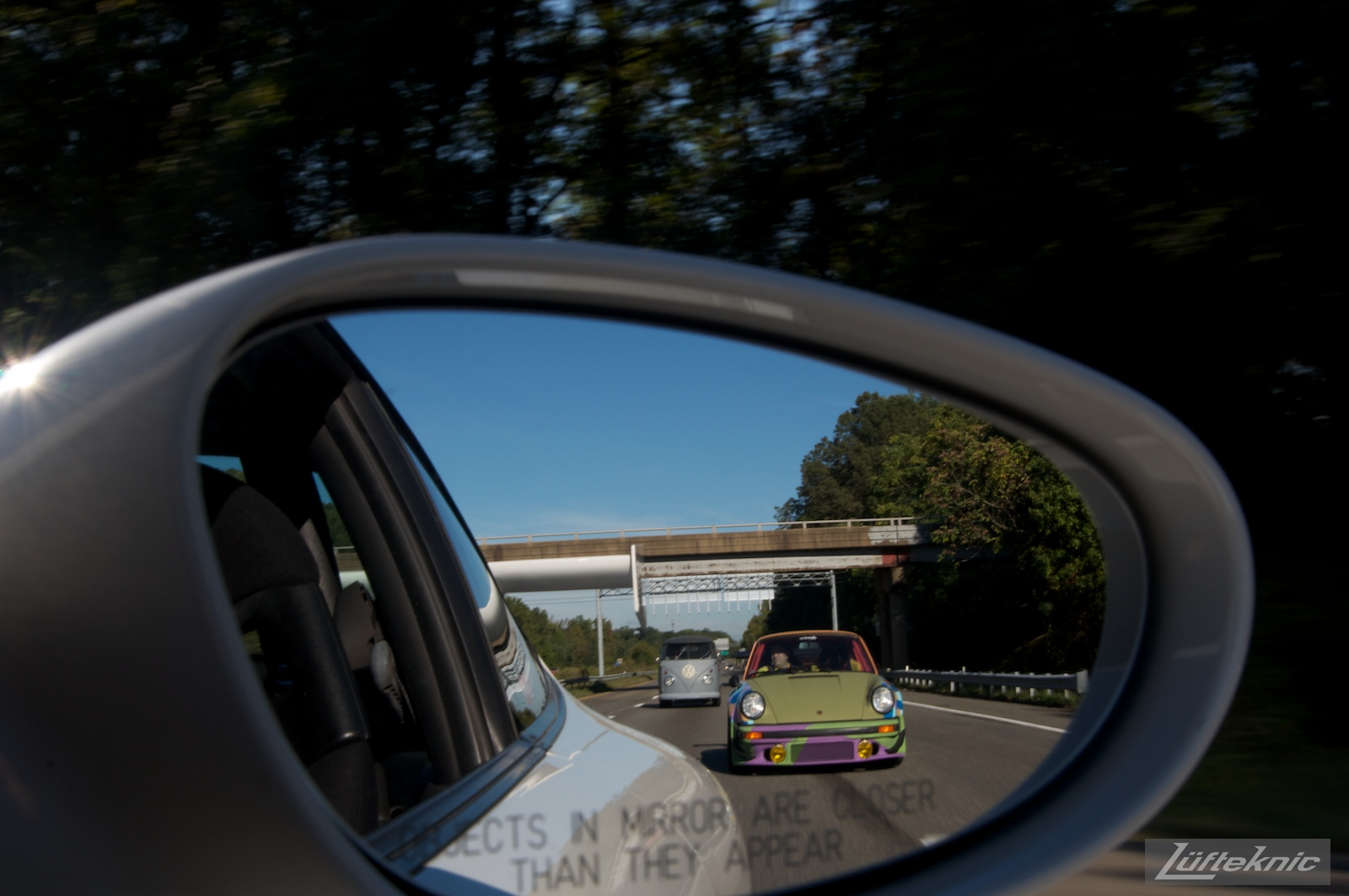 Side view mirror showing the Lüfteknic #projectstuka Porsche 930 Turbo driving to h2o international car show.