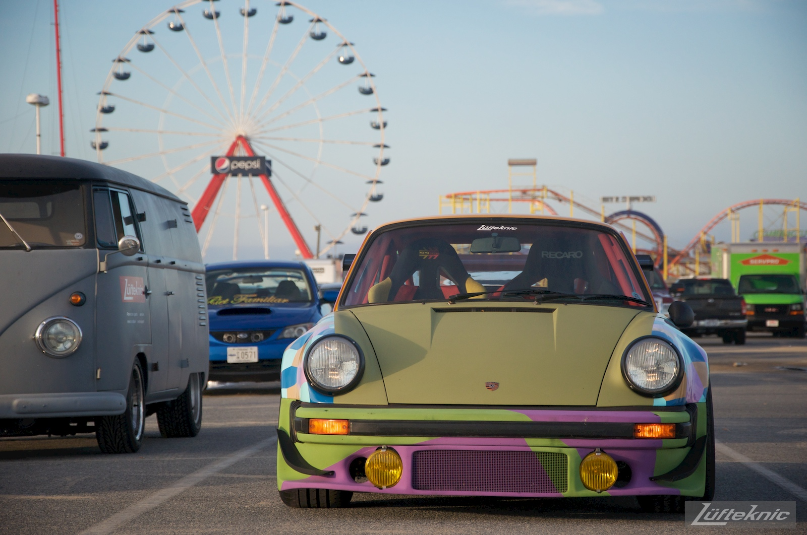 The Lüfteknic #projectstuka Porsche 930 Turbo and porschebus with a ferris wheel and roller coaster behind.