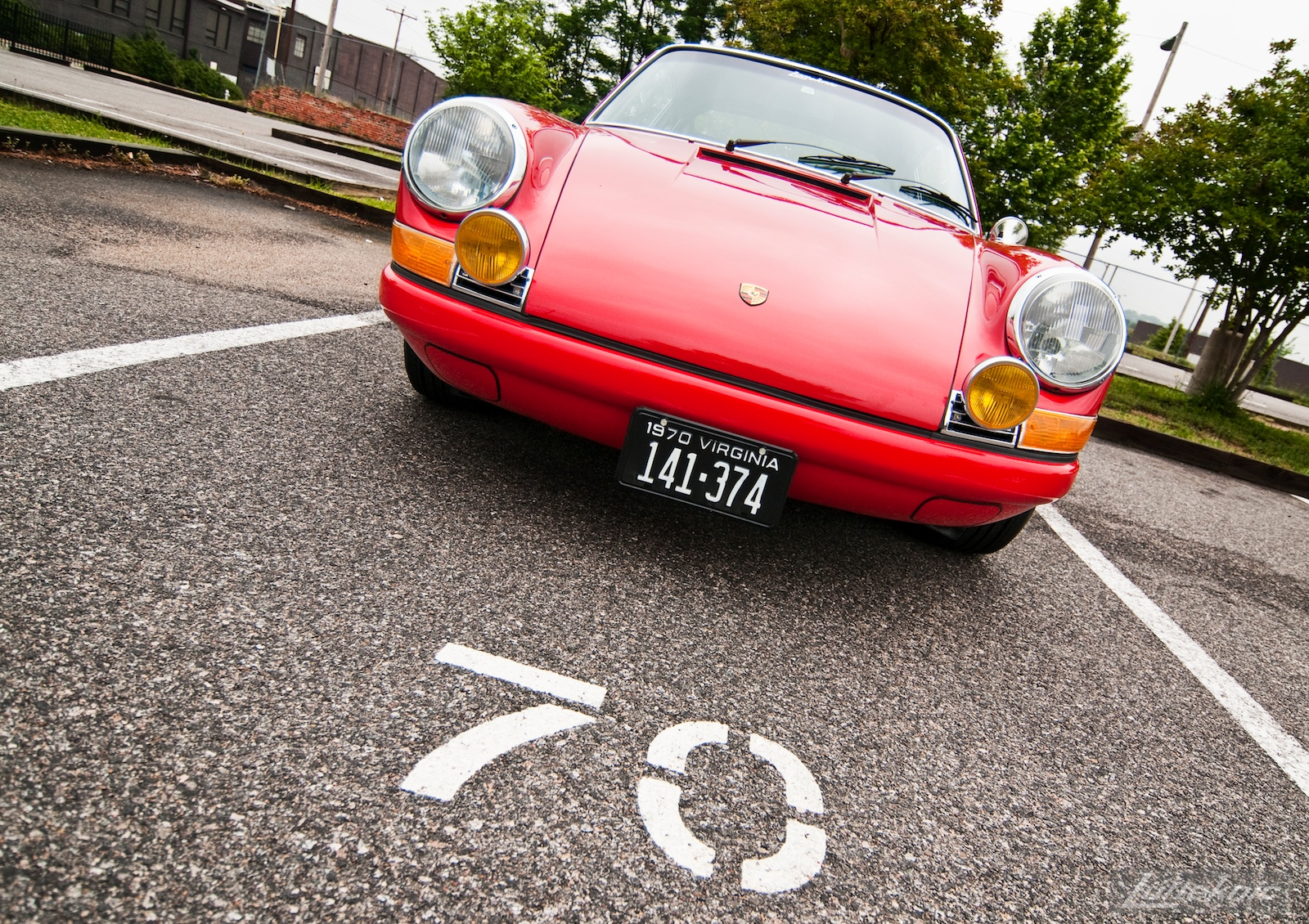 A red 1970 911E in a parking space marked 70.