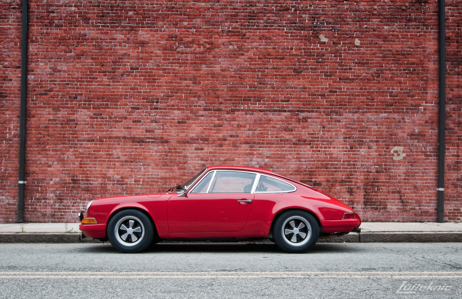 A red 911 profiled on a red brick wall.