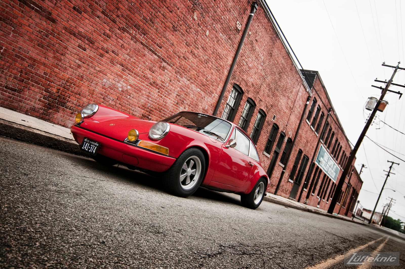 A red 1970 911E in front of an old brick building.