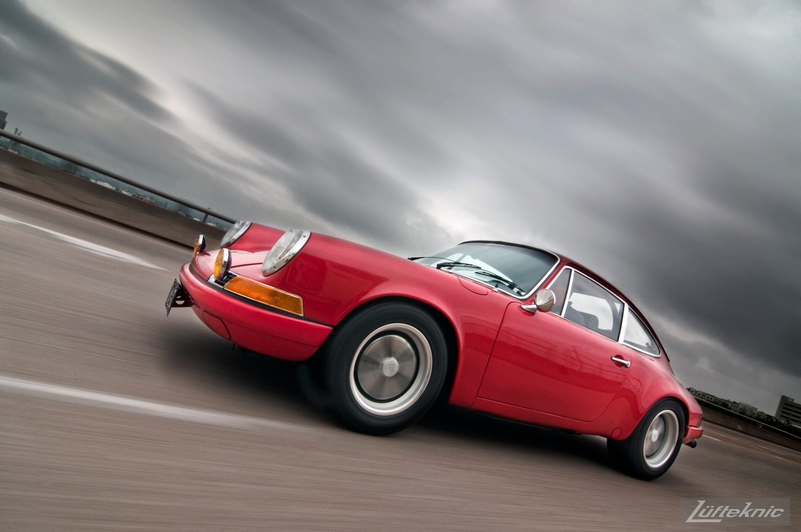 A pacing shot of a red 911E with dark clouds