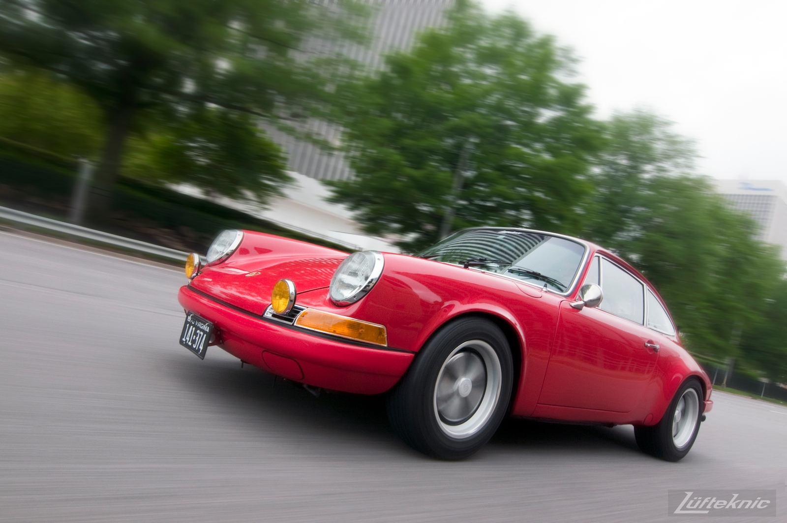 A pacing shot of a red 911E with trees and a blurred background.