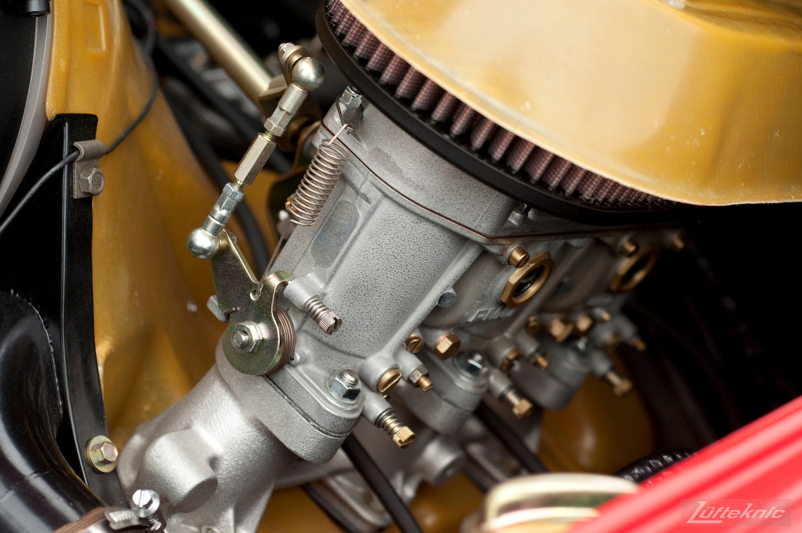 A close up picture of PMA carburetors and gold covers.