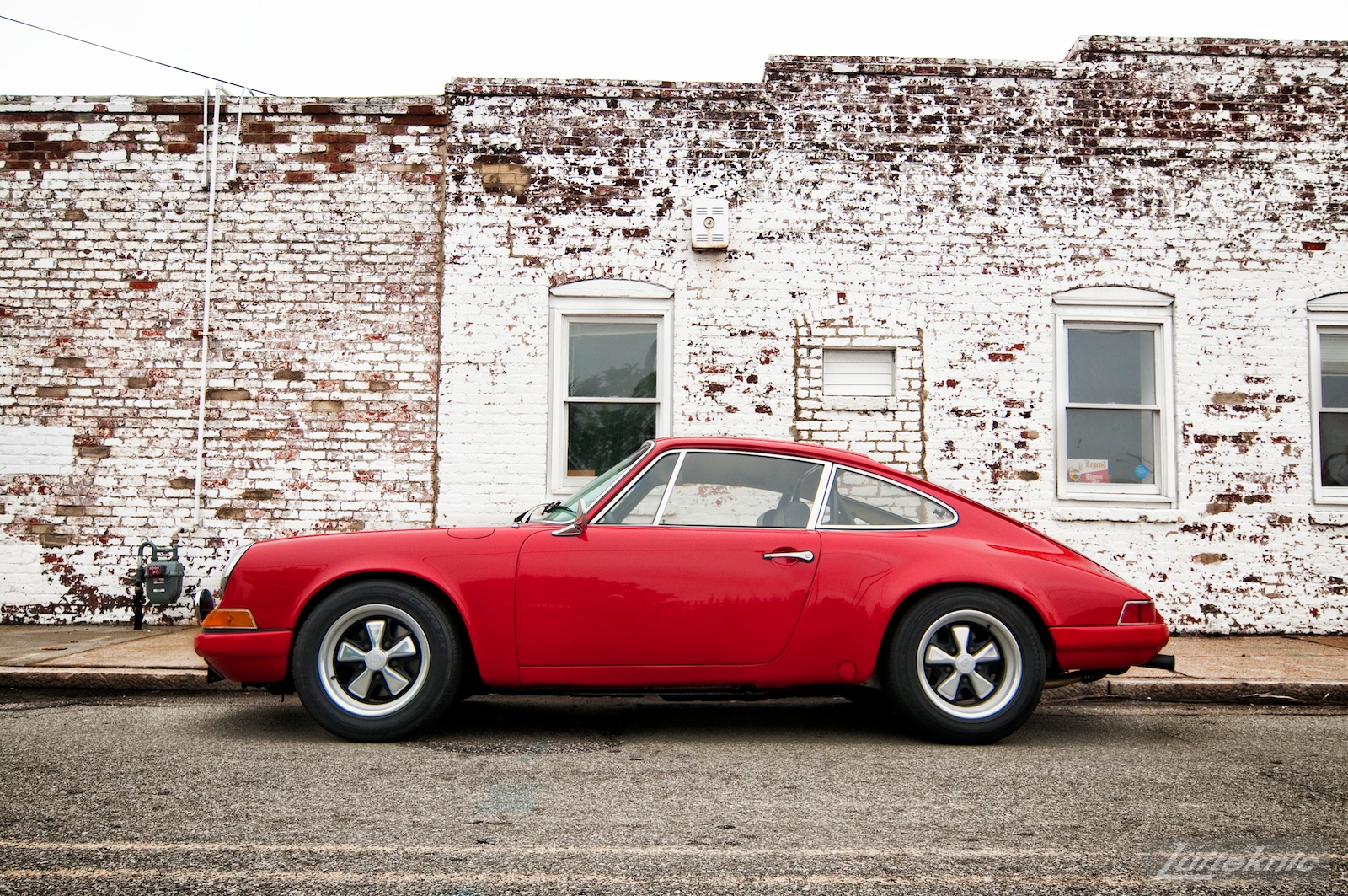 Bright red 1970 911E in front of a white wall.