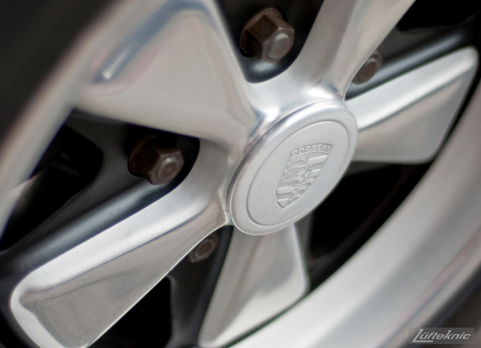 A close up picture of a Porsche center cap on a Fuchs wheel