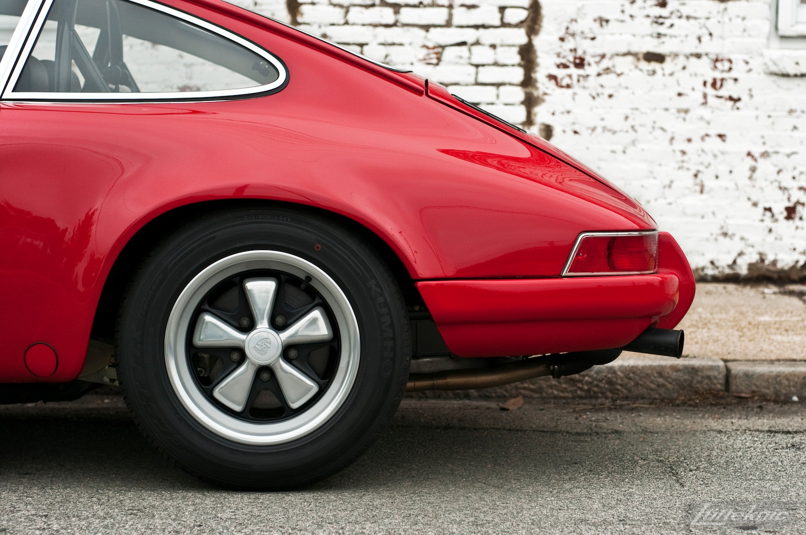 The rear wheel and fender on a red 911E
