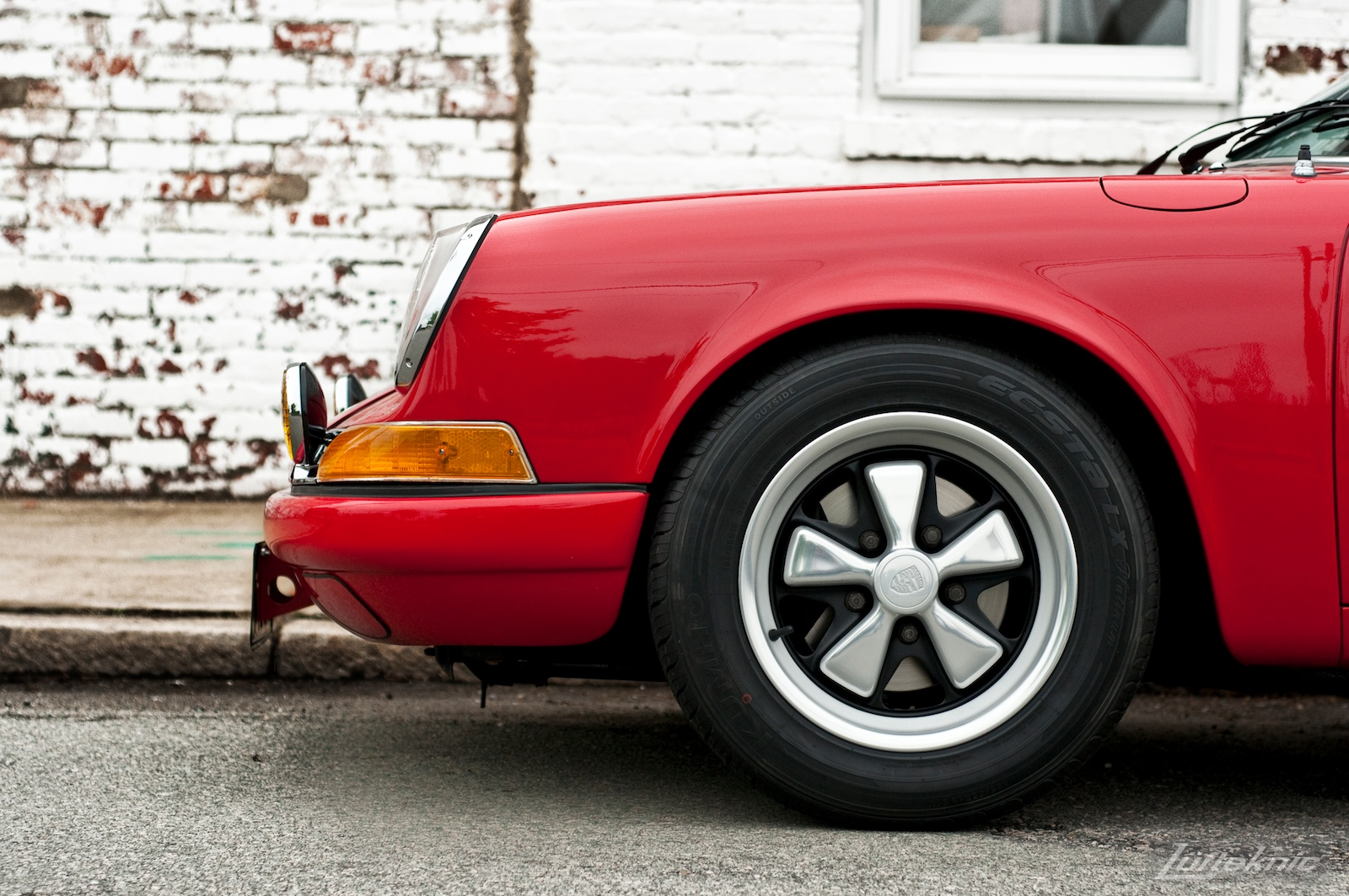 The front wheel and fender on a red 911E in profile.