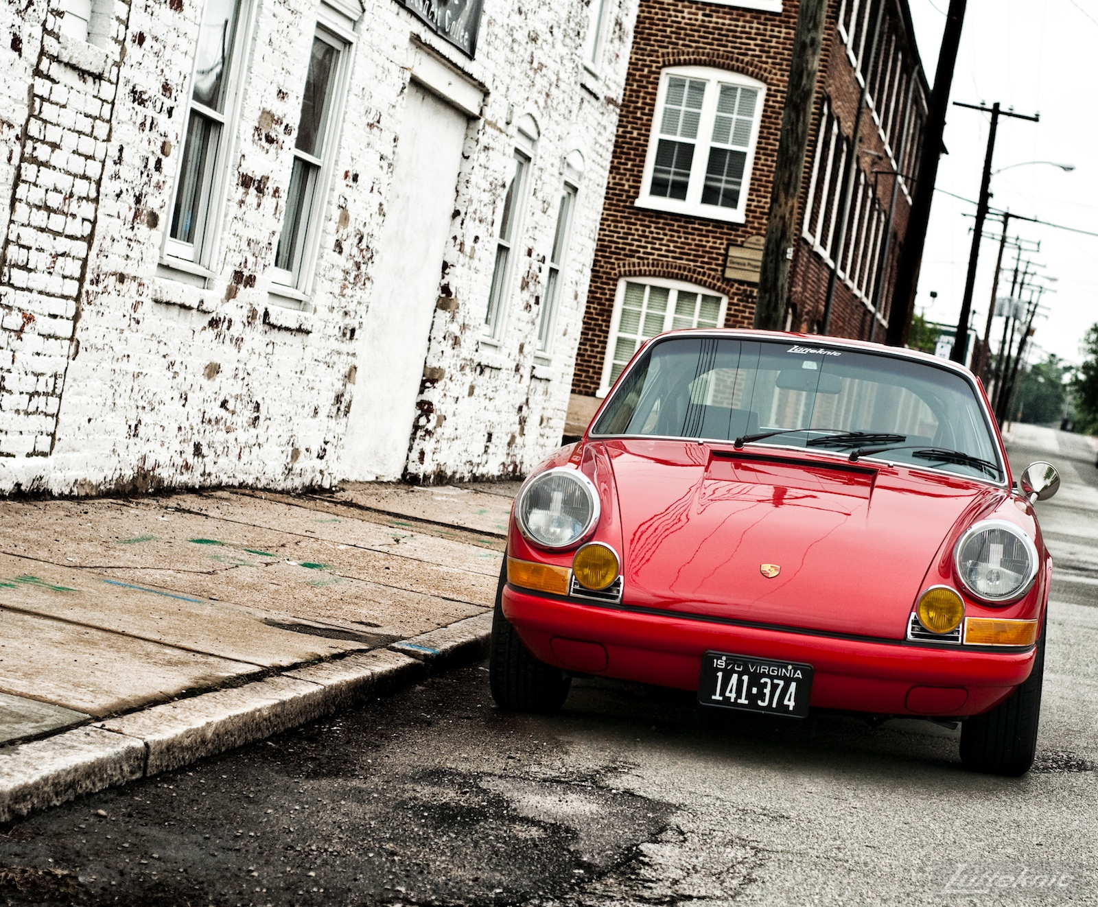 Bright red 1970 911E in front of a white wall and brick buildings.