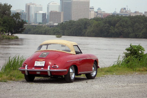 A red Porsche roadster pictured from the rear next to a lake.