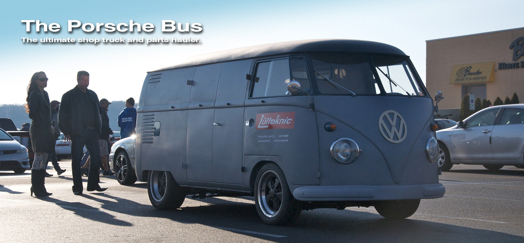 Porschebus slider image, showing the bus in a parking lot with people looking on