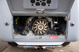 The engine lid raised on a 1956 VW bus showing the Porsche 3.6L twin plug engine installed.
