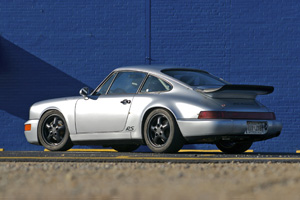 Porsche 964 sports car in front of a blue wall
