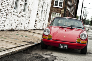 A red 911E parking near a white brick building with atmosphere.