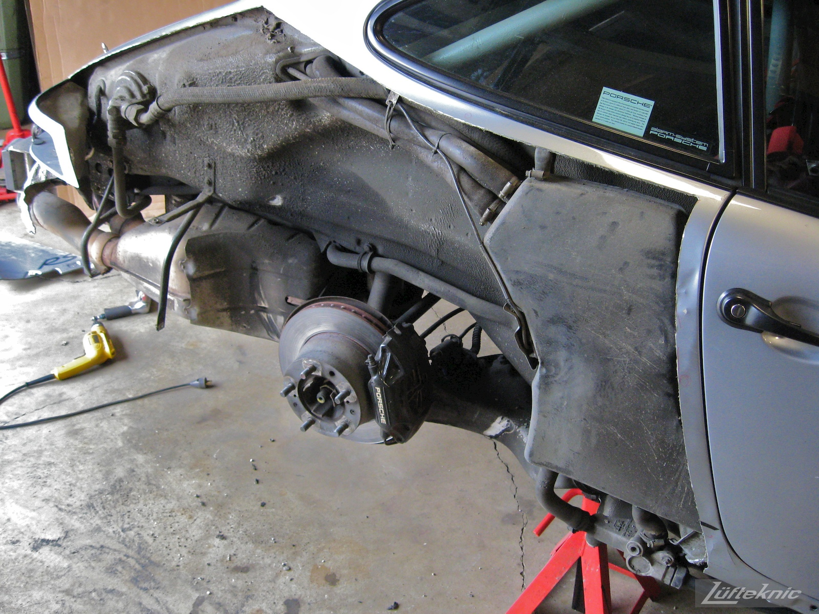 A cut away rear quarter panel showing the suspension and exhaust on the 964 RS America project
