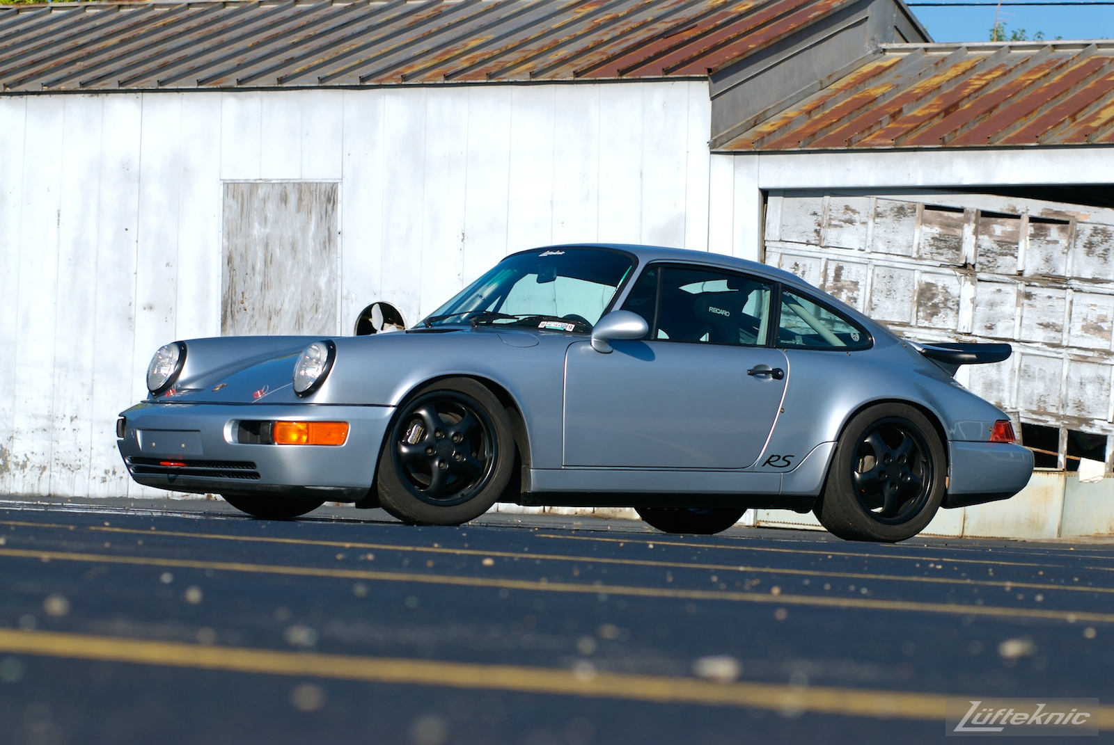 The 964 RS America shown from the front in a parking lot with a dilapidated garage in the background.