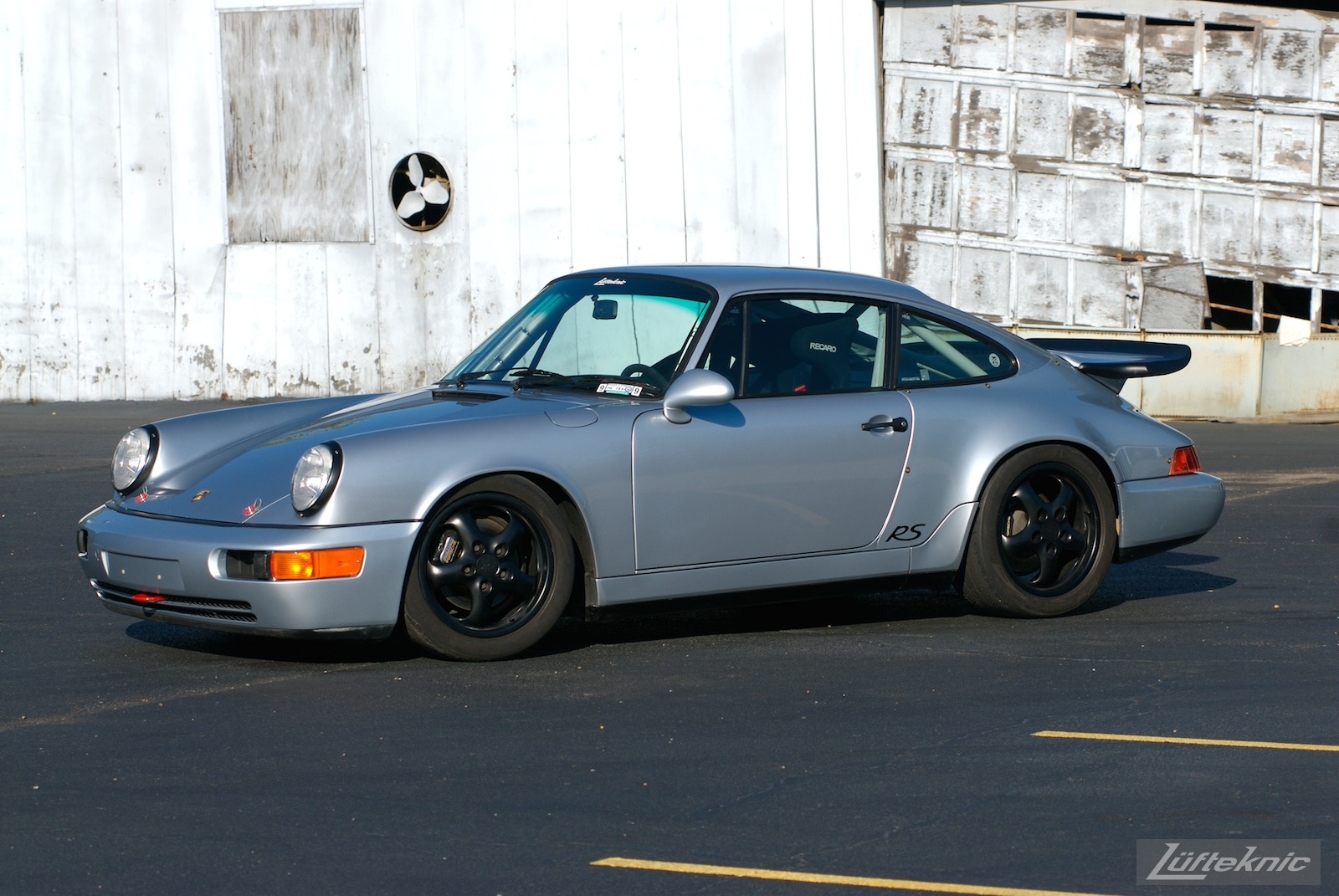 The 964 RS America in a parking lot with a dilapidated garage in the background.