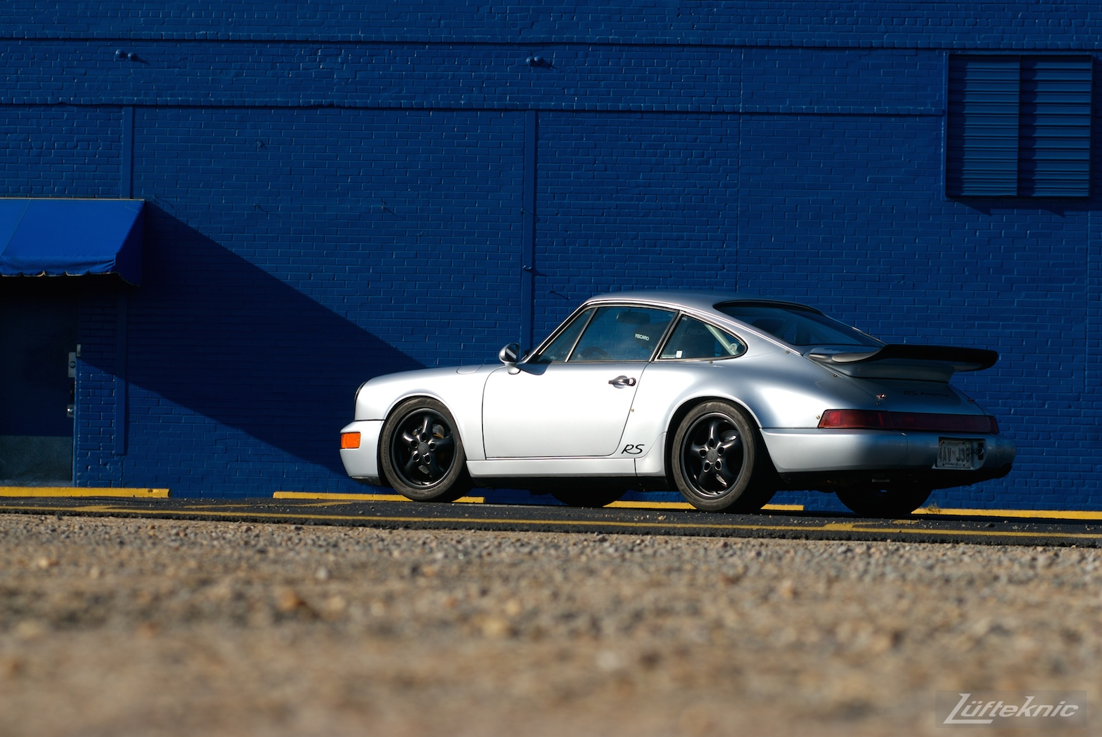 A Big blue wall with a beautiful silver Porsche 911 RS America