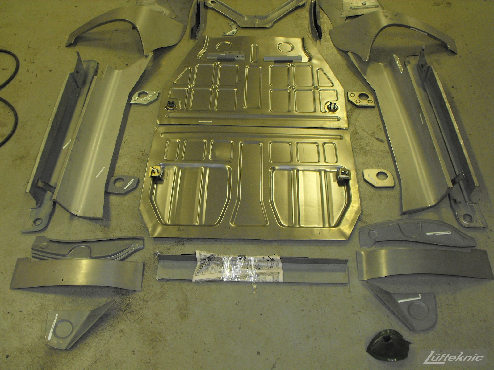 New floors and panels laid out on the ground for a 1961 Porsche 356B Roadster restoration.
