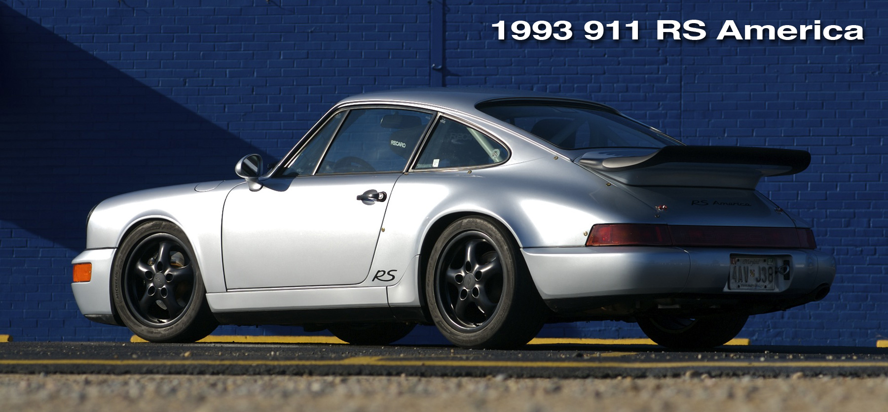 964 RS America header image with the silver car shown in front of a blue wall.