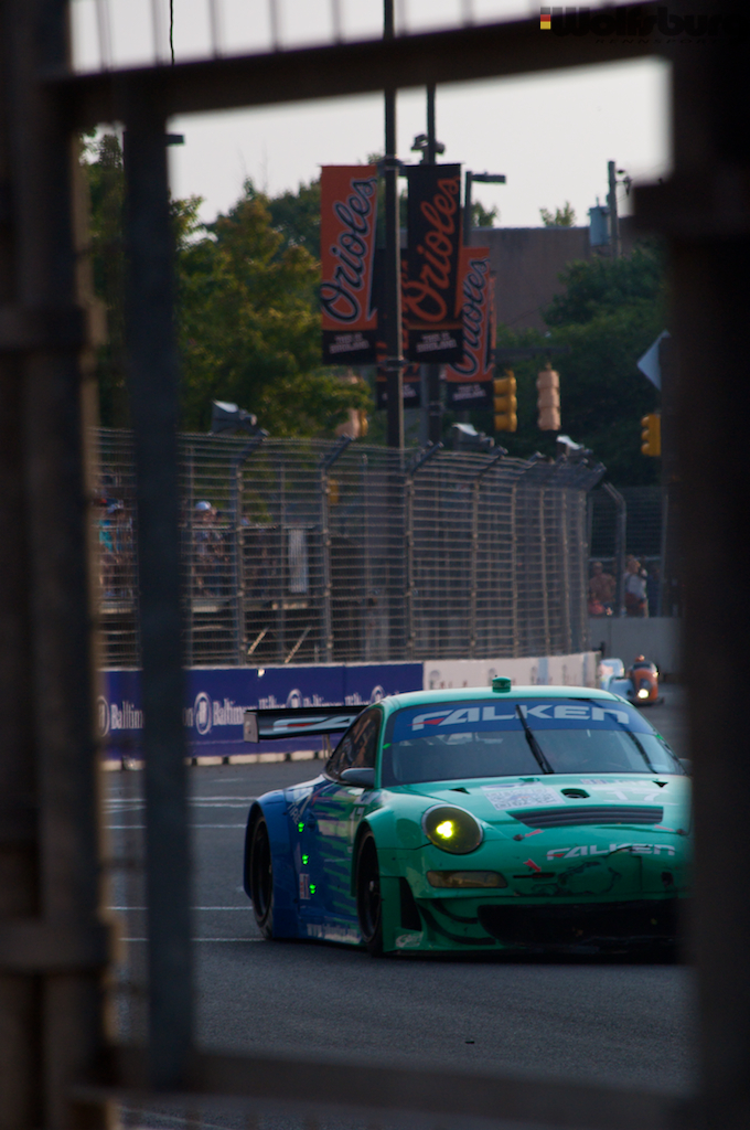 The iconic teal and blue Falken Tire Porsche 911 RSR at Baltimore with Orioles banners by the stadium.