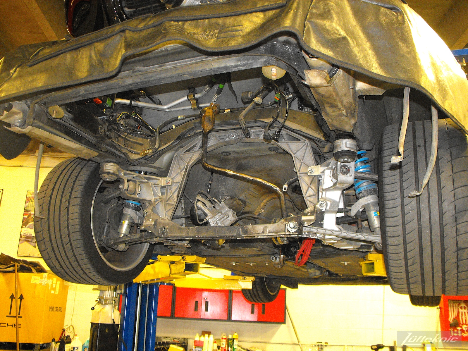 A Porsche 993TT underbody with the engine removed and rear tires and suspension exposed.