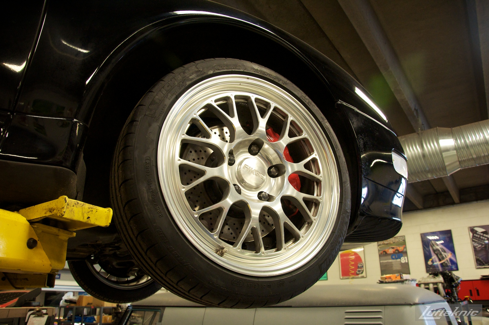A close up of a Fikse wheel on the front of a 993 Turbo on a lift in the Lufteknic shop.