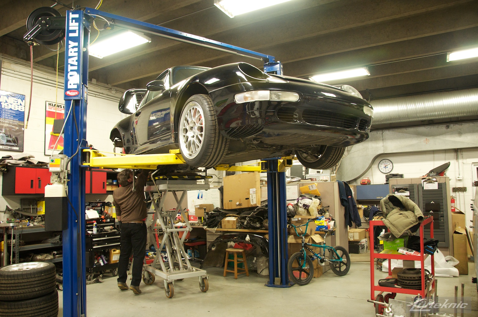 A shot from the front showing a 993 Turbo on a lift with the engine stand lifting the driveline into the car