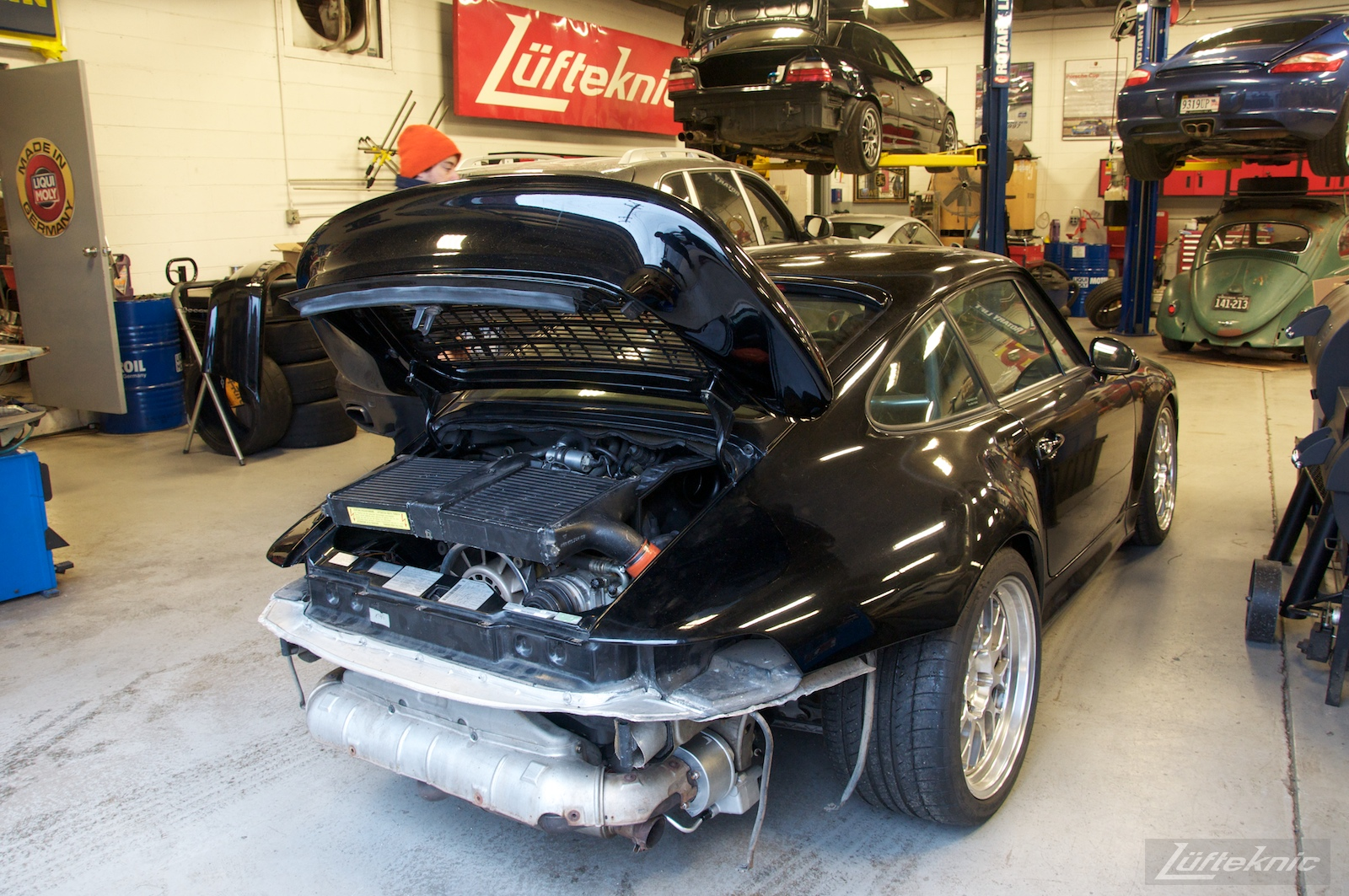 993 Turbo with no rear bumper sitting staged inside the Lufteknic shop with other cars inside the shop.