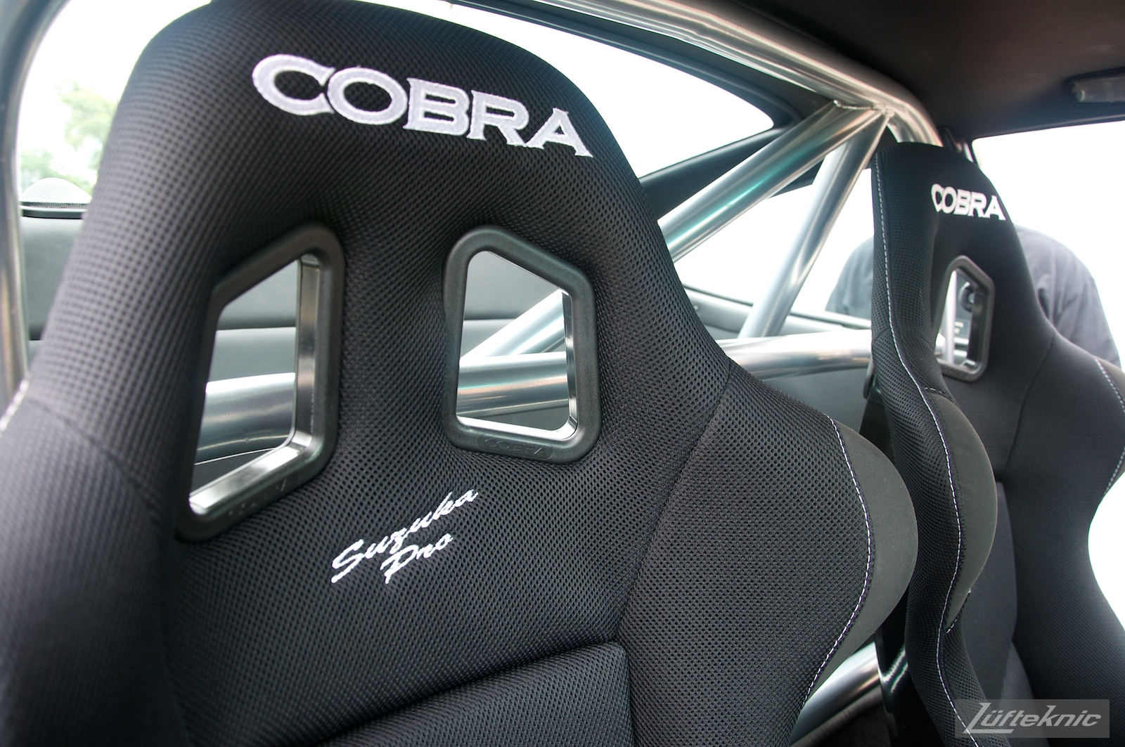Cobra seats and roll bar mounted in a black 993 Porsche Turbo.