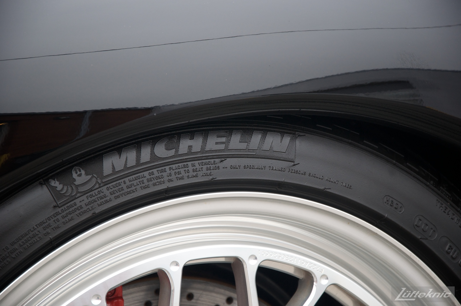 Detail shot of the Michelin Pilot tire and Fikse wheel on a black 993 Porsche Turbo.